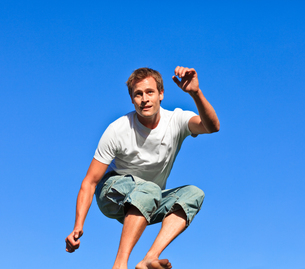 Smiling man jumping against a blue backgroundの素材 [FYI00482744]