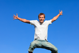 Confident man jumping against a blue backgroundの素材 [FYI00482745]