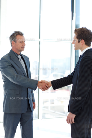 Senior and junior businessman shaking hands in agreementの素材 [FYI00482756]