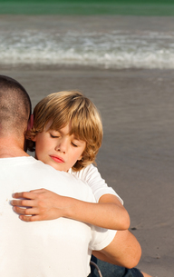 Son and his father hugging on the beachの写真素材 [FYI00482794]