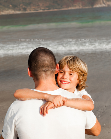 Son and father hugging on the beachの写真素材 [FYI00482797]