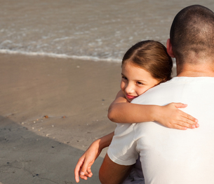 Daughter and her father hugging on the beachの写真素材 [FYI00482798]