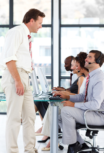 Senior manager talking to a worker in a call centerの写真素材 [FYI00482807]