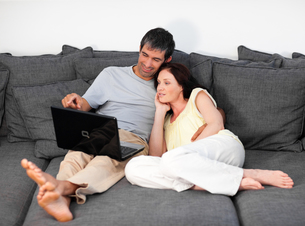 Lovely couple using a laptop on a sofaの写真素材 [FYI00482840]