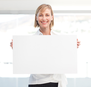 Beautiful woman holding empty white boardの写真素材 [FYI00482850]