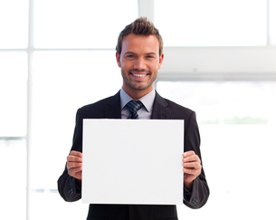 Smiling businessman holding a white cardの写真素材 [FYI00482851]