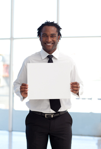 Smiling businessman holding a white cardの写真素材 [FYI00482852]