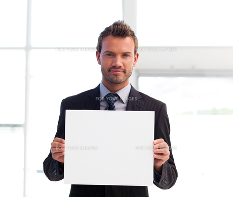 Serious businessman holding a white cardの素材 [FYI00482855]