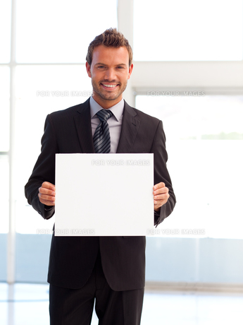 Handsome smiling businessman showing a white cardの写真素材 [FYI00482856]