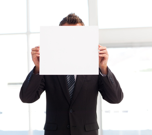 Businessman holding a white card in front of his faceの写真素材 [FYI00482857]