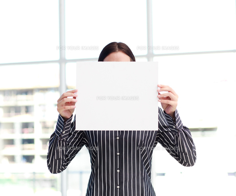 Smiling woman showing a big business card in front of her faceの写真素材 [FYI00482858]