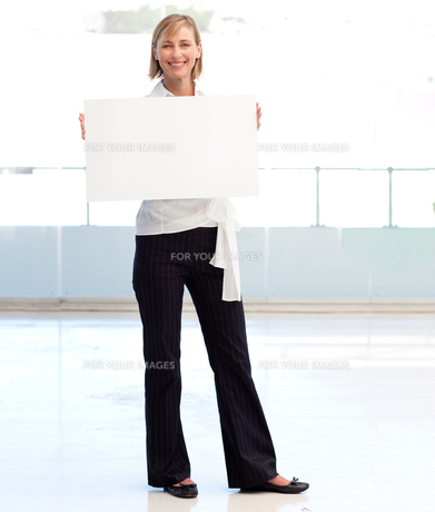 Businesswoman holding a white  cardの写真素材 [FYI00482859]