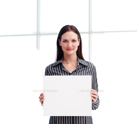 Pretty woman holding a white sheet of paperの写真素材 [FYI00482860]