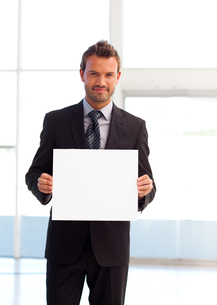 Friendly businessman holding a white cardの写真素材 [FYI00482861]