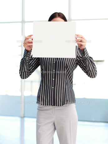 Businesswoman showing a white card in front of her faceの写真素材 [FYI00482863]
