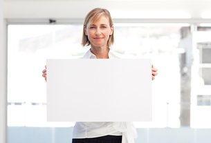 Mature woman showing a big business cardの写真素材 [FYI00482866]