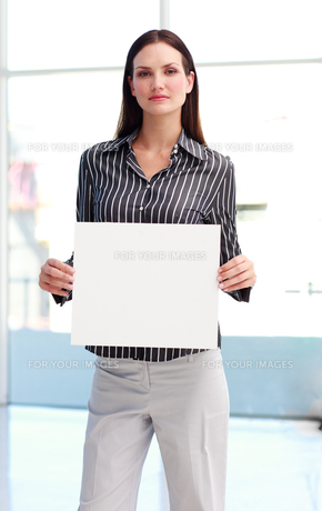 Confident woman showing a big business cardの素材 [FYI00482867]