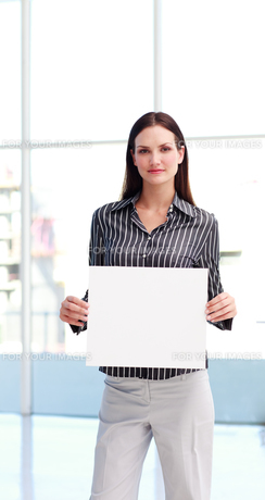 Serious woman showing a big business cardの写真素材 [FYI00482868]