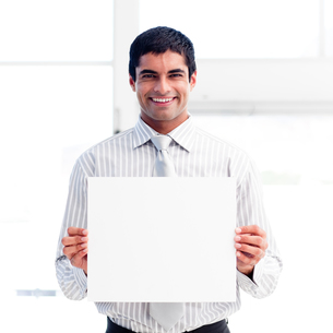 Portrait of a smiling businessman holding a white cardの写真素材 [FYI00482869]