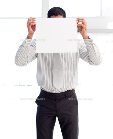 Businessman showing a white card covering his faceの素材 [FYI00482871]