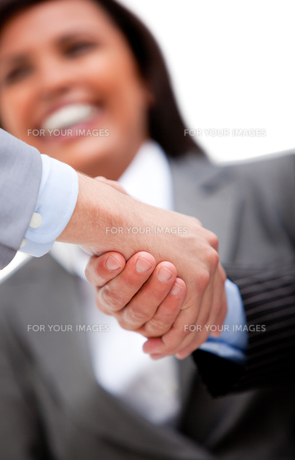 Smiling businesswoman looking at her partners shaking handsの素材 [FYI00482876]