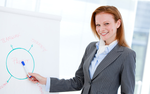 Confident businesswoman pointing at a white boardの素材 [FYI00482877]