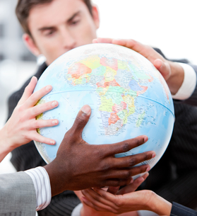 Close up of a business team holding a terrestrial globeの素材 [FYI00482879]