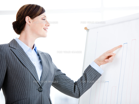 Portrait of a laughing businesswoman talking about a graph during a meetingの素材 [FYI00482901]