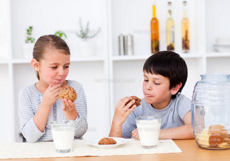 Smiling Siblings eating cookiesの写真素材 [FYI00482908]