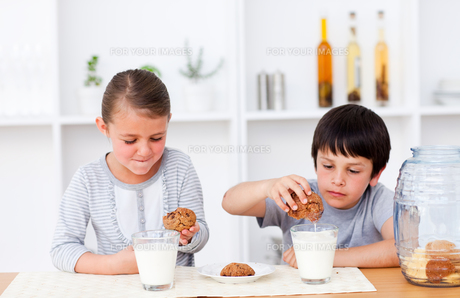 Brother and sister eating cookies and drinking milkの写真素材 [FYI00482909]