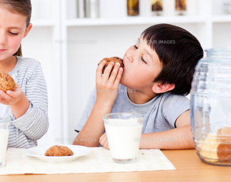 Smiling Siblings eating biscuits and drinking milkの写真素材 [FYI00482910]