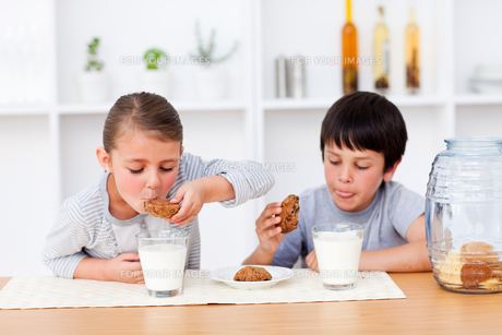 Happy Siblings eating biscuits and drinking milkの写真素材 [FYI00482911]