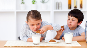 Happy brother and sister eating biscuits and drinking milkの写真素材 [FYI00482912]