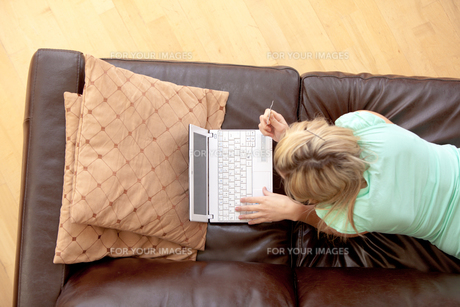 Bright woman using a laptop on a sofaの写真素材 [FYI00482929]