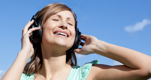 Cheerful woman is listening music outdoorの写真素材 [FYI00482939]