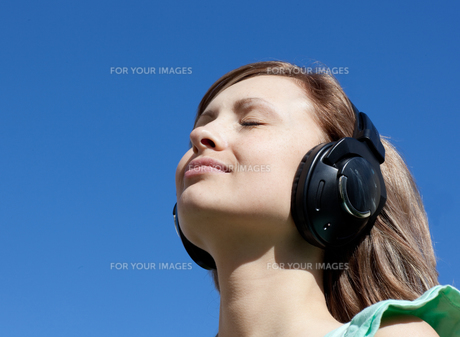 Cute woman is listening music outdoorの素材 [FYI00482940]