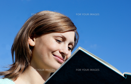 Delighted woman is reading a book outdoorの写真素材 [FYI00482941]