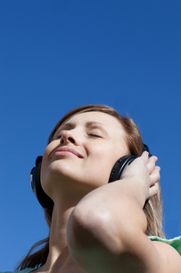 Radiant woman is listening music outdoorの素材 [FYI00482942]