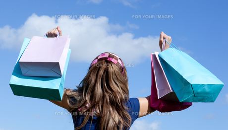 Cute woman holding shopping bags outdoorの素材 [FYI00482943]