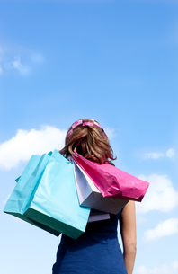 Smiling woman holding shopping bags outdoorの素材 [FYI00482946]