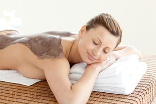Radiant woman enjoying a mud skin treatmentの素材 [FYI00482948]