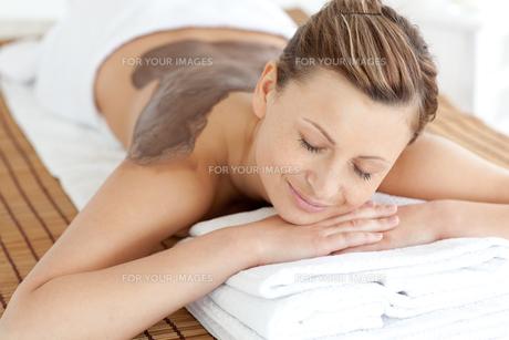 Relaxed woman enjoying a mud skin treatmentの素材 [FYI00482949]
