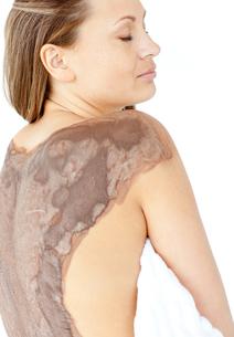 Portrait of a bright woman enjoying a mud skin treatmentの写真素材 [FYI00482950]