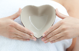 Close up of a woman holding a bowl in the shape of a heartの素材 [FYI00482959]
