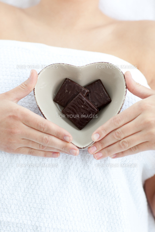 Close up of a woman holding a bowl in the shape of a heart with chocolateの素材 [FYI00482960]