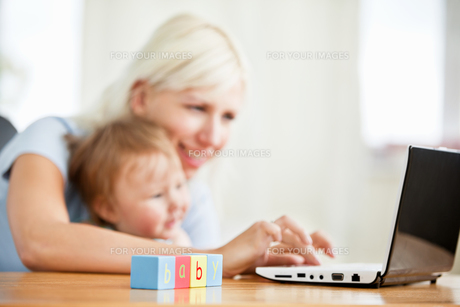 Smiling woman surfing on the internet with her girl in the livingroomの写真素材 [FYI00482990]