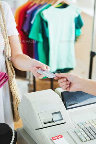 Close up of a cute woman paying with her credit cardの素材 [FYI00483003]
