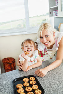 Smiling girl eating cookieの写真素材 [FYI00483042]