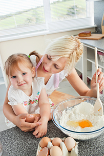 Mother and smiling child baking cookiesの写真素材 [FYI00483053]