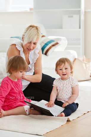 Goodlooking woman working with her children at laptopの写真素材 [FYI00483066]